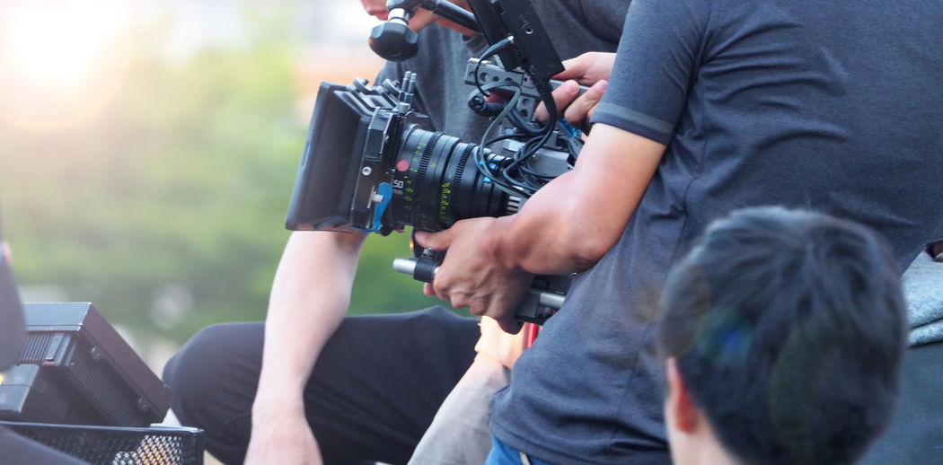 Blurry image of movie shooting or video production and film crew team with camera equipment at outdoor location and light flare effect. Behind The Scenes Production Camera - Photographic Equipment Camera Operator Location Men Photography Themes Shooting Technology Video Video; Film; Production; Camera; Movie; Equipment; Crew; Making; Professional; Television; Man; Shoot; Studio; Filming; Operator; Media; Cameraman; Photographer; Cinema; Tv; People; Outdoor; Director; Scene; Photography; Digital; Work; Background; Set; Te