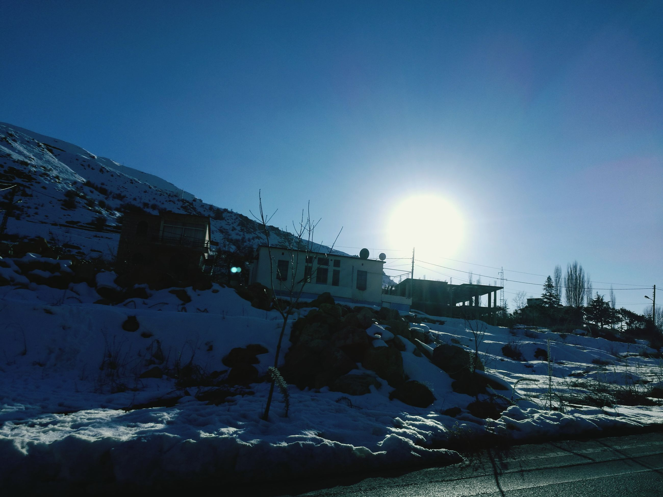 cold temperature, winter, snow, built structure, sky, outdoors, nature, frozen, leisure activity, winter sport, building exterior, mountain, sun, vacations, beauty in nature, city, architecture, ski lift, no people, day