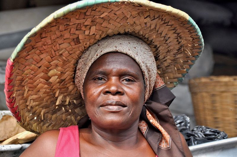 Close-up portrait of mature woman wearing straw hat outdoors