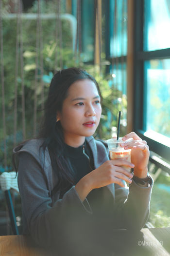 Portrait of young woman drinking glass at restaurant