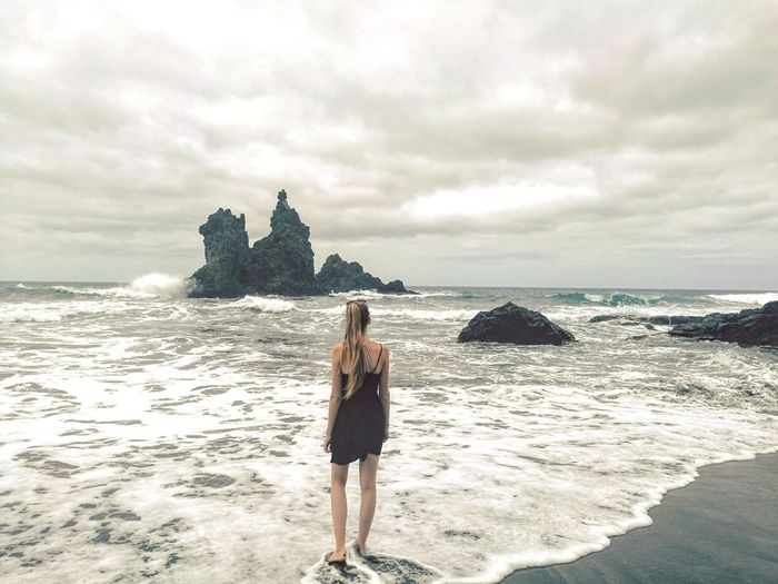 Rear View Of Young Woman Standing On Shore Against Cloudy Sky