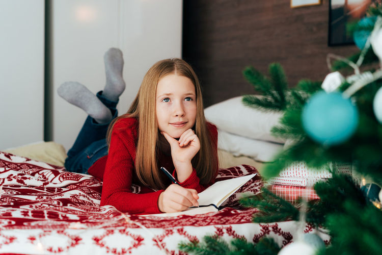 Portrait of teenage girl sitting at home