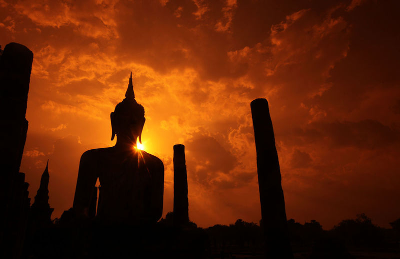 Low angle view of silhouette buddha statue