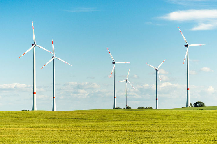 Windmills on grassy field against sky