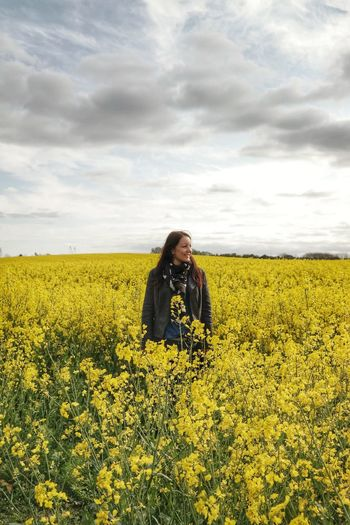 Woman standing in rapeseed field against cloudy sky