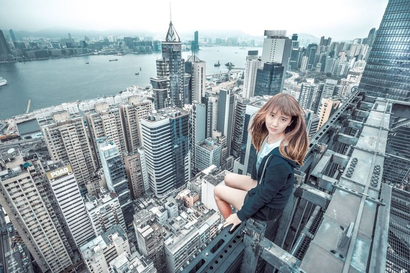 Woman with cityscape against sky