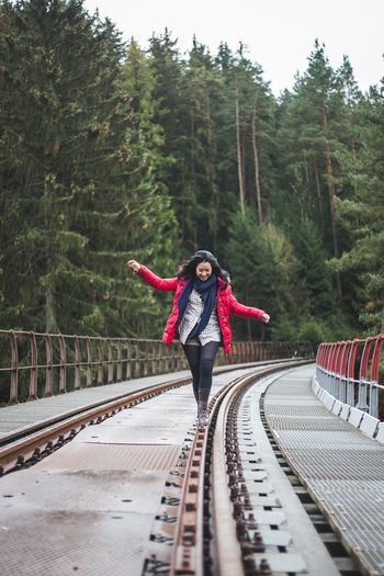 Full length of woman standing on footbridge in forest