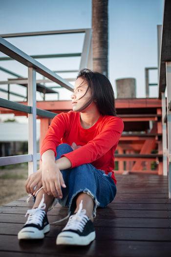 Full length of teenage girl sitting on railing
