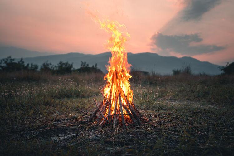 Bonfire on field against sky during sunset