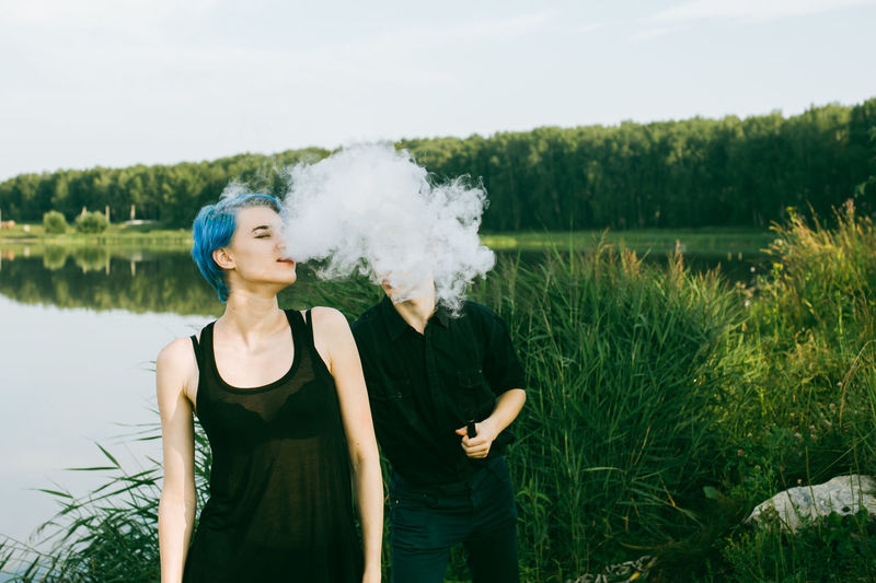 Friends smoking electronic cigarette at lakeshore