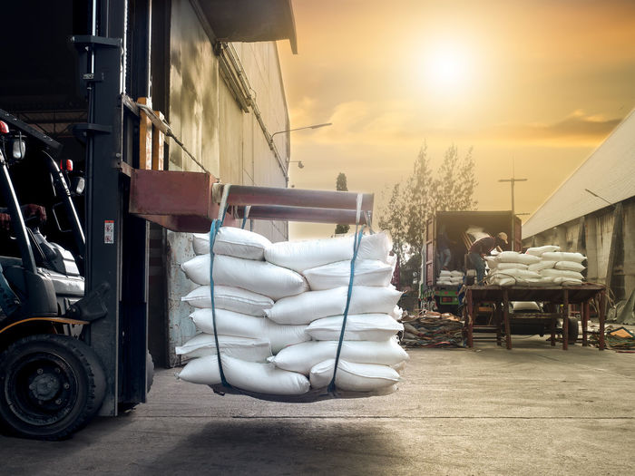 Forklift handling sugar bags outside from warehouse for stuffing into container for export. Container Conveyor Belt Forklift Rice Sugar Architecture Bags Day Export Freight Handling Import Labor Land Vehicle Mammal Men One Person Outdoors Season  Shipping  Stuffing Tapioca Transportation Truck Warehouse
