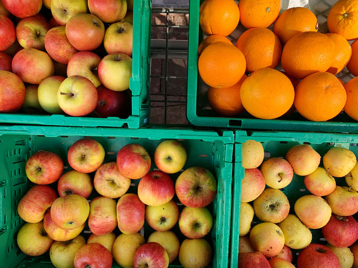 High angle view of apples and oranges for sale in weekly market