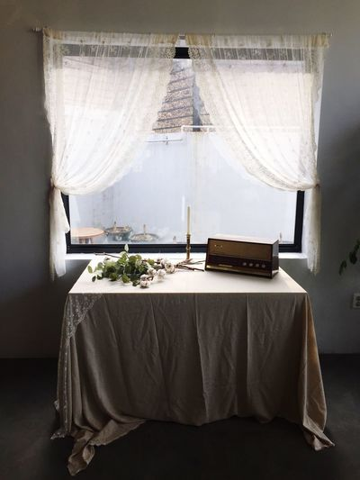 Radio with flowers and candle arranged on table against window