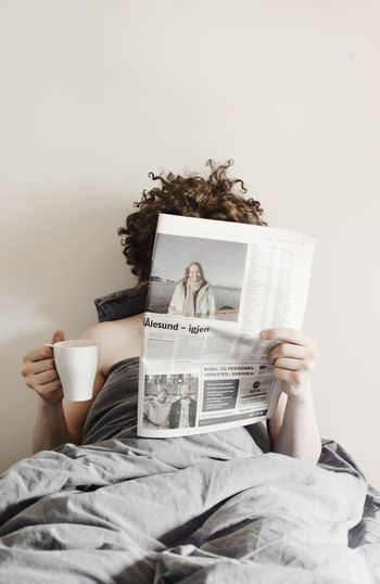 Midsection of woman reading book on bed