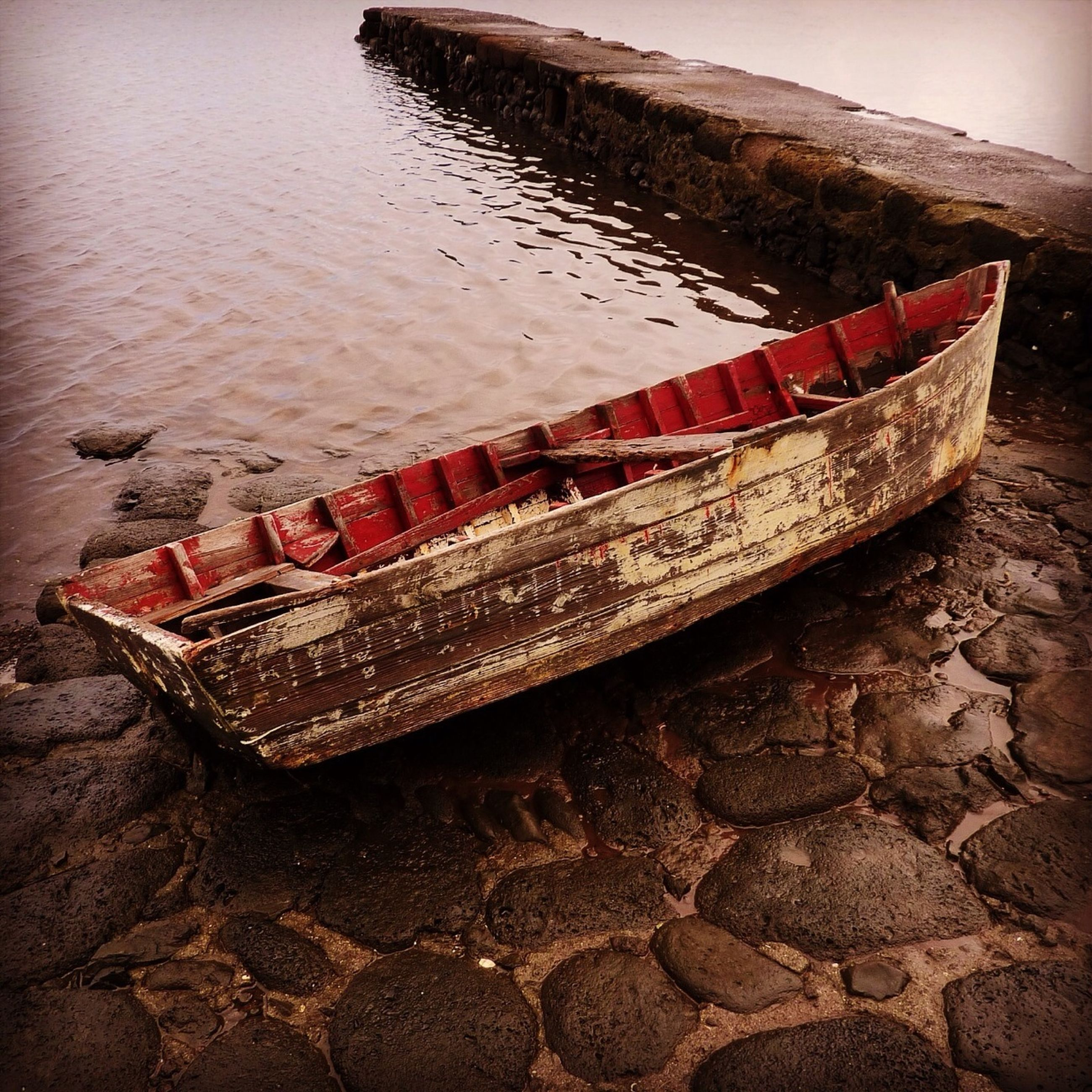 water, nautical vessel, boat, transportation, moored, mode of transport, lake, abandoned, red, sea, day, outdoors, beach, high angle view, nature, tranquility, no people, rock - object, shore, river