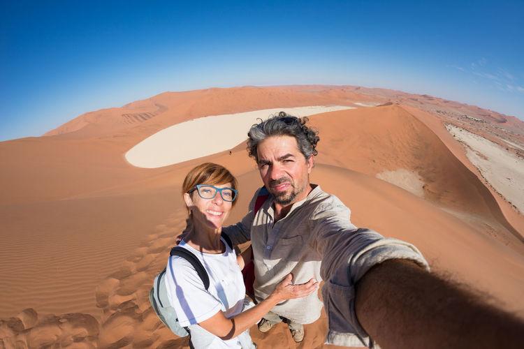 High angle portrait of couple standing on desert against sky