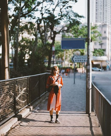Portrait of young woman holding railing against bridge in city