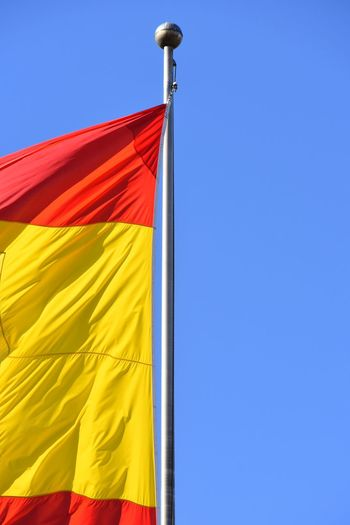 Spanish flag in Constitution Avenue Blue Sky Clear Sky Constitution Identity Low Angle View Monument Pole Red And Yellow Spanish Flag