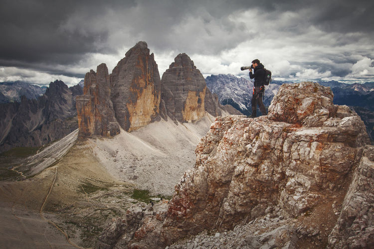 Man photographing on mountain against cloudy sky