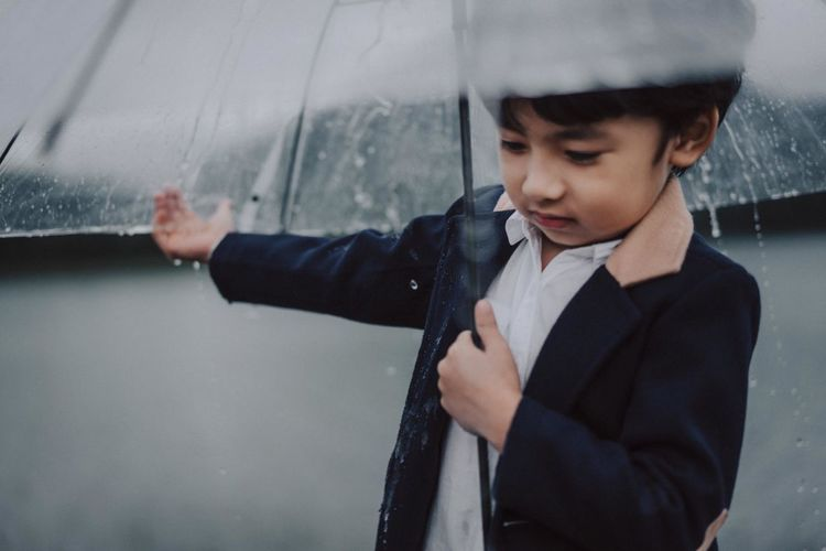 Boy with umbrella standing against lake during rainfall
