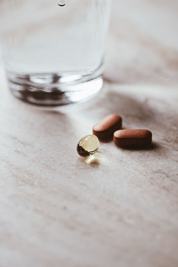 Close-up of pills with glass of water on table