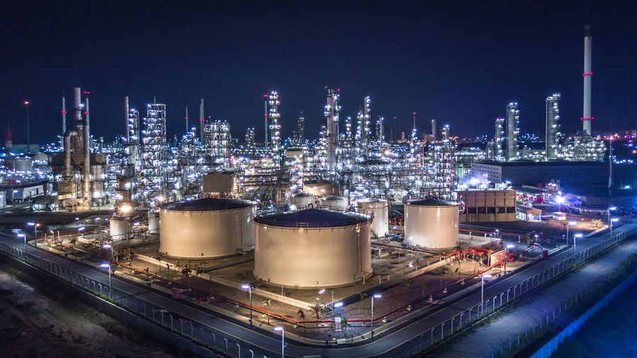 High angle view of illuminated factory in city at night