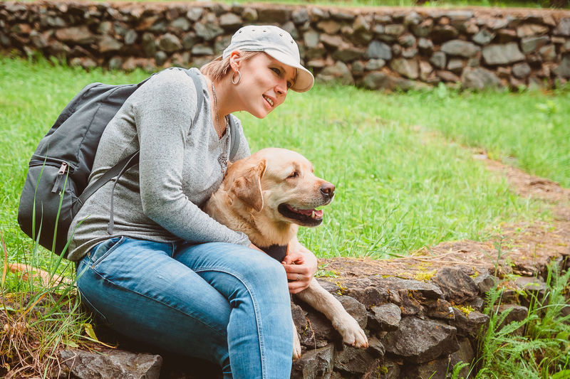 A girl with a backpack is sitting on the lawn hugging a labrador retriever and smiling. outdoor