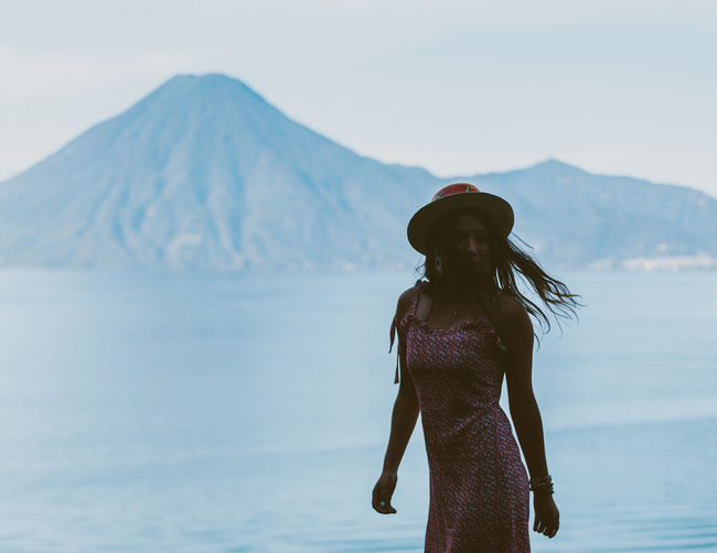 Woman wearing hat standing against sea and mountain