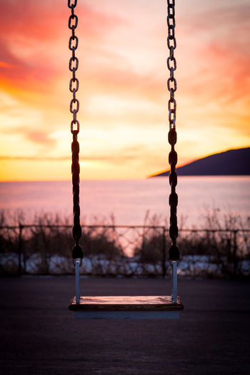 Close-up of swing at playground against sky during sunset