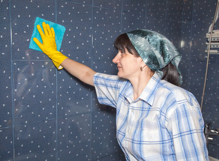 Woman wiping tiled wall