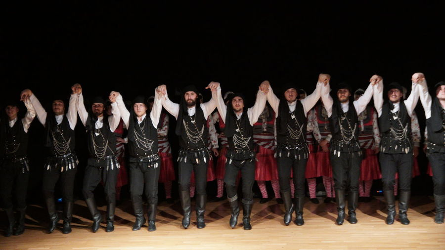 Group Of People Real People Performance Men Large Group Of People Indoors  Crowd Standing Full Length Arts Culture And Entertainment In A Row Studio Shot Males  Togetherness Women Occupation Adult Young Adult Performing Arts Event Black Background Stage Arms Raised
