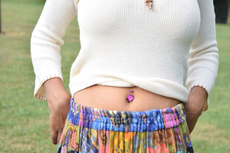 Midsection Of Woman With Belly Ring In Park