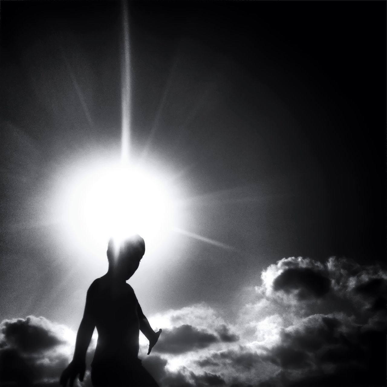sunbeam, silhouette, real people, one person, low angle view, lifestyles, childhood, leisure activity, sun, outdoors, sunlight, sky, standing, boys, nature, cloud - sky, day, one boy only, men, beauty in nature, people