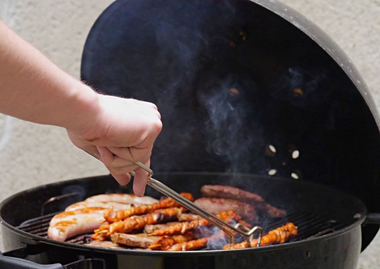Cropped hand of man cooking meat on barbeque grill