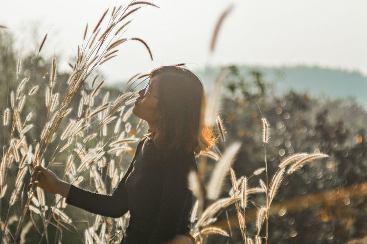 Side view of woman with plants on field against sky