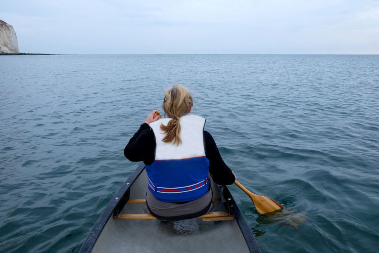 Rear view of woman rowing boat in sea against sky
