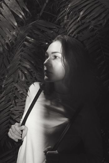 Thoughtful woman looking away while standing against plants at night