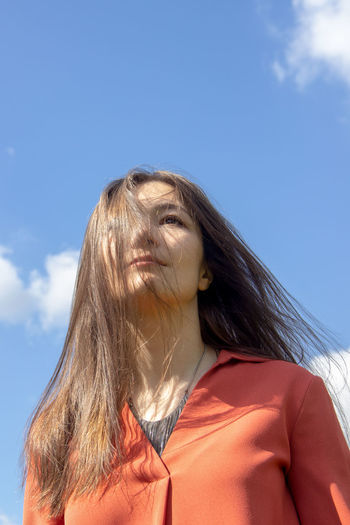 Low angle portrait of woman against sky