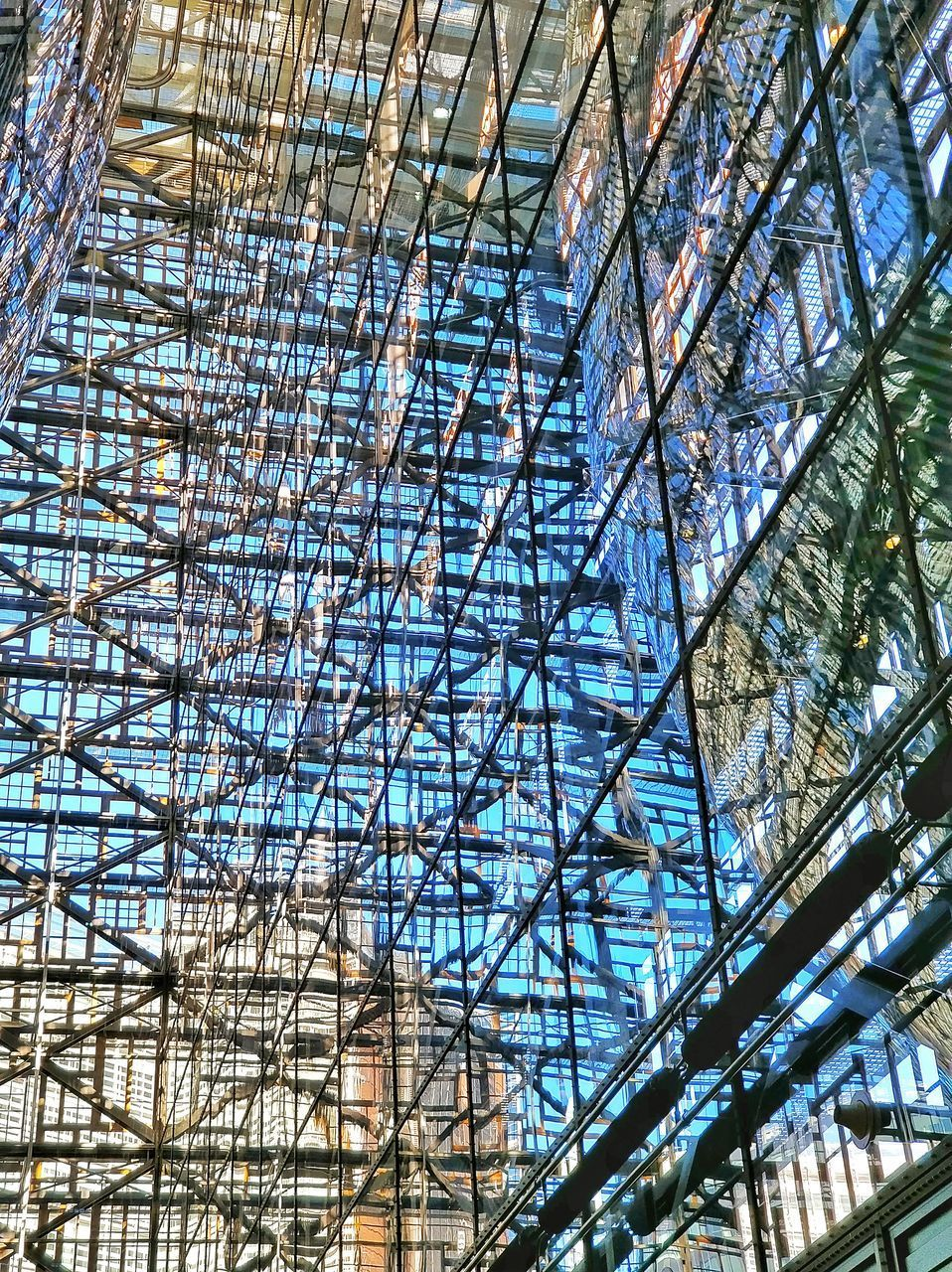 LOW ANGLE VIEW OF GLASS CEILING ON BUILDING