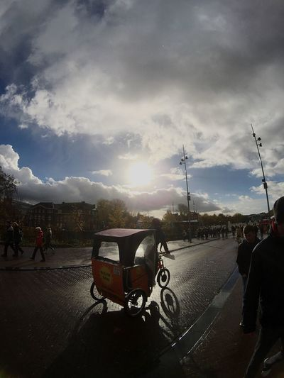 Transportation Sky Mode Of Transport Land Vehicle Cloud - Sky Road Sunlight Street Outdoors Real People Day Motorbike Moment Lens Netherlands Amsterdam IPhoneography Light And Shadow Street Photography Large Group Of People People And Places Superfish Transportation Lifestyles Sun Lens Flare