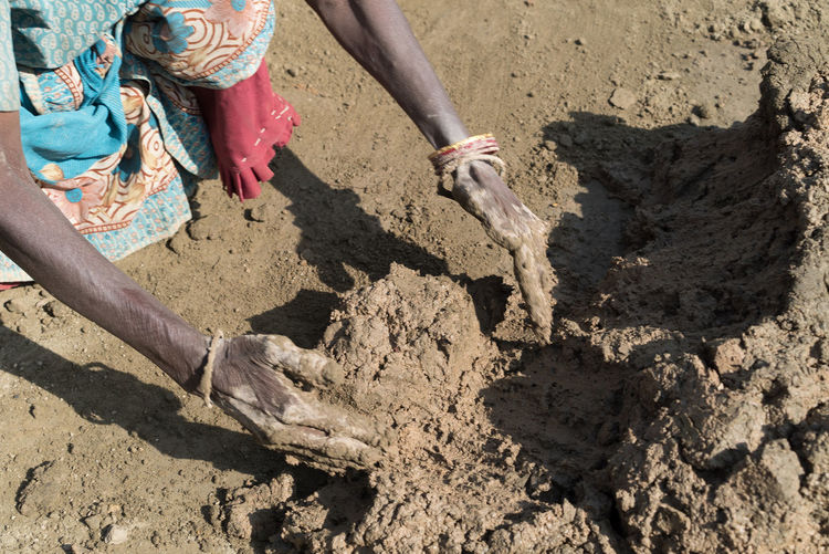 Low section of person working in mud