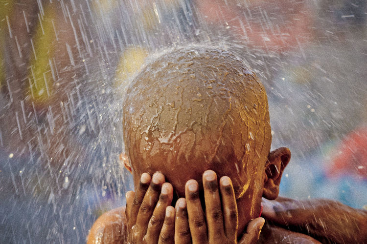 BATU CAVES, MALAYSIA - 9TH FEBRUARY 2017; A Hindu devotee takes a shower during Thaipusam festival to fulfil their vows and offer thanks to the deities. Batu Caves -Malaysia Child Childhood Children Only Close-up Day Hindu Culture Hindu Gods Hinduism Human Body Part Human Hand One Person Outdoors People Shower Thaipusam Water