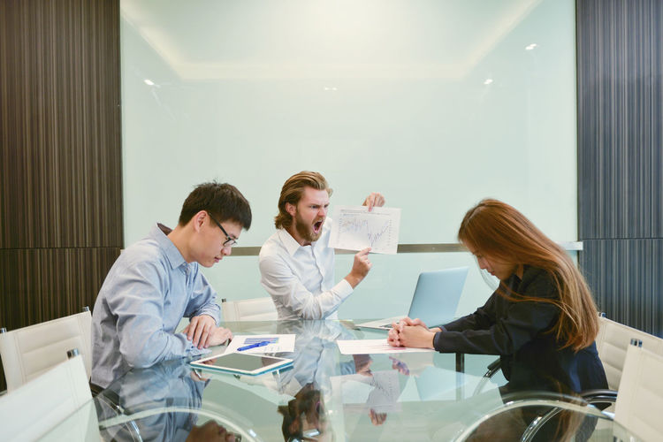 Blonde business man blaming Asian employee in meeting room Blonde Meeting Office Suit Working Boss Business Businessman Colleague Coworker Day Indoors  Meeting Room Men Mid Adult Men Office People Real People Sitting Teamwork Three People Togetherness Well-dressed Western Women Working Young Adult Young Women