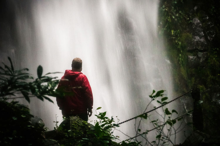 A man watches a water fall in La Fortuna, Costa Rica Beauty In Nature Costa Day Nature One Person Outdoors People Rain Real People Rear View Tree Water Water Reflections Waterfall