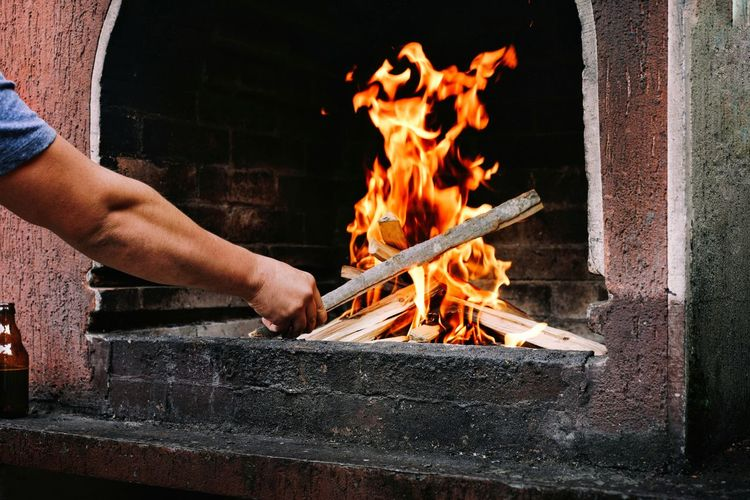 Midsection of man holding burning fire on wood on barbecue grill