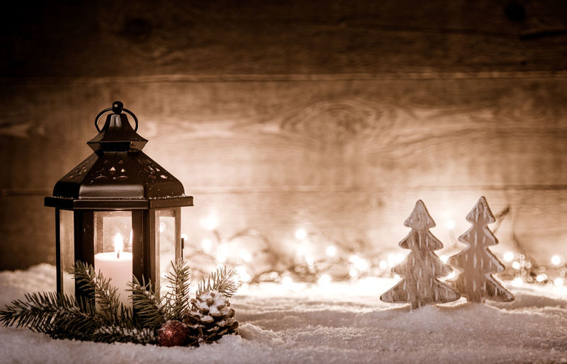 Illuminated lamp on snow covered christmas tree during winter