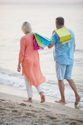 Rear view of mature couple with shopping bags walking on shore at beach