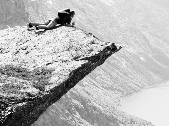 High Angle View Of Hiker Lying On Rocky Mountain