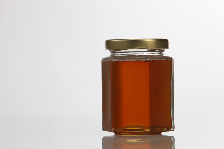Close-up of syrup in bottle against white background