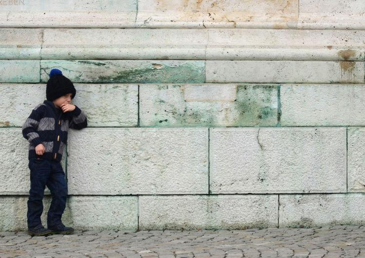Boy standing on brick wall